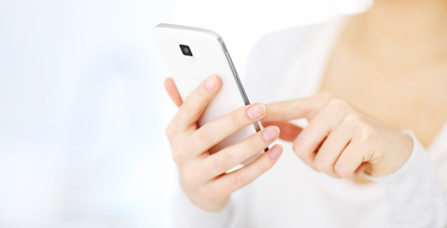 Close up shot of a woman in white using a mobile phone